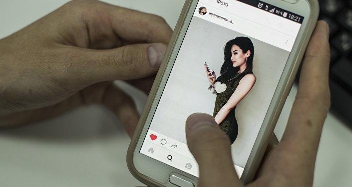 Пользователь смотрит страницу Instagram Айжан Асемовой с экрана смартфона