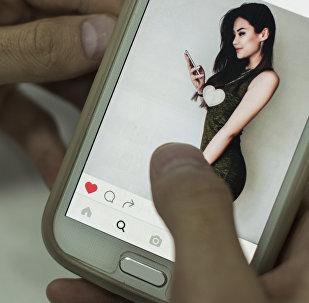 Айжан Асемованын Instagram баракчасын карап жаткан адамдын архивдик сүрөтү
