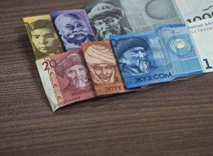 Национальная валюта Кыргызстана разным номиналом на столе. Архивное фото