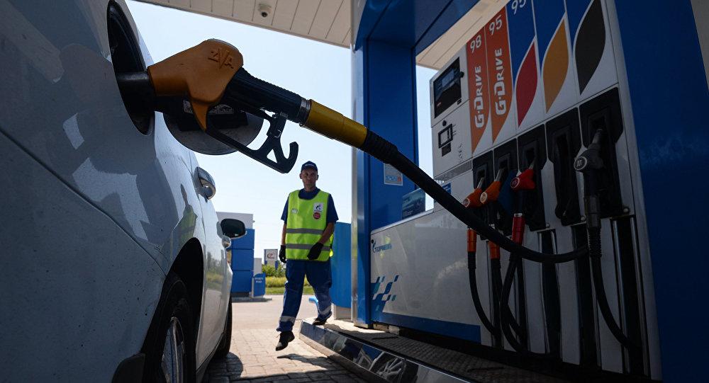 Сотрудник автозаправочной станции (АЗС) компании Газпром нефть заправляет автомобиль клиента. Архивное фото