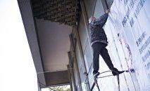 Работник развешивает билборд в Бишкеке. Архивное фото