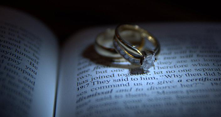 Обручальные кольца на книге. Архивное фото