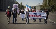 Участники митинга с транспарантами в поддержку арестованных членов оппозиции на площади Ала-Тоо в Бишкеке
