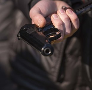 Пистолет в руке мужчины во время учебных стрельб в день открытых дверей для школьников в Бишкеке