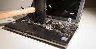 Удар молотком об клавиатуру ноутбука. Архивное фото