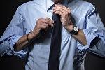 Архивное фото мужчины который завязывает галстук