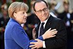 Президент Франции Франсуа Олланд приветствует канцлера Германии Ангела Меркель во время встречи  в Париже