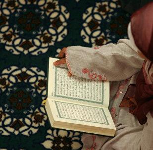 Куран китебин окуп жаткан аял. Архив