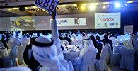 Человек поднимает руку, чтобы делать ставку в аукционе по продаже автомобильных номеров в Дубае, Объединенные Арабские Эмираты. Архивное фото