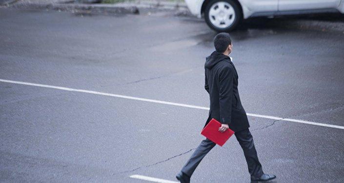 Парень с папкой переходит дорогу в городе Бишкек. Архивное фото
