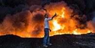 Мужчина делает селфи на фоне огня. Архивное фото