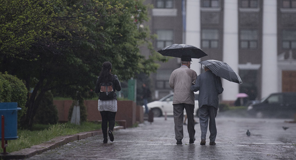 Прохожие с зонтом во время дождя. Архивное фото