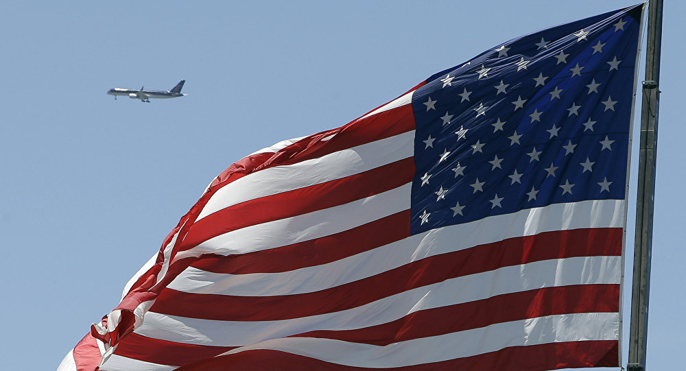 Летящий самолет на фоне флага США. Архивное фото