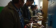 Мужчины вносят мясо в зал во время празднования свадьбы. Архивное фото