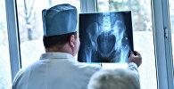 Врач смотрит рентген снимок тазовой кости. Архивное фото