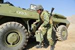 Военнослужащий КР устанавливает мобильное и компактное средство связи на БТР
