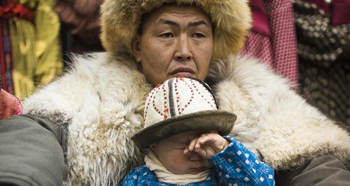 Мужчина с ребенком в национальных костюмах. Архивное фото