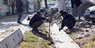 Сотрудник муниципальной службы во время ремонта ирригационной сети по улице Суюнбаева ниже проспекта Чуй