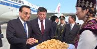 Кытайдын премьерин кучак толо гүл жана боорсок менен тосуп алышты