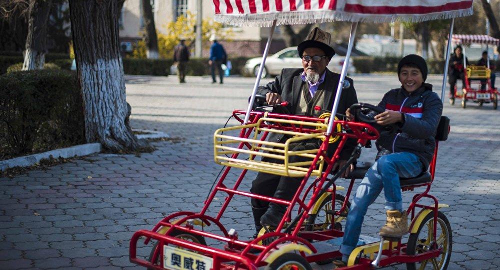 Велосипед тээп бараткан бала жана кары адам. Архив