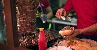 Мужчина готовит гамбургер в одном из точек быстрого питания в Бишкеке. Архивное фото