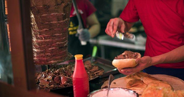 Архивное фото работника фастфуда, который готовит гамбургер