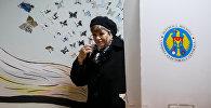 Женщина во время президентских выборов на избирательном участке в Кишиневе