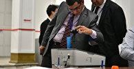 Международные наблюдатели фотографируют электронную урну. Архивное фото