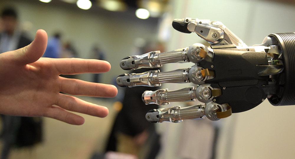 Мужчина притягивает руку к руке робота. Архивное фото