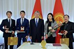 Президет КР Алмазбек Атамбаев во время поздравление создателей фильма Завещание отца и дизайнера-модельера Аиды Робертовой
