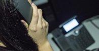 Стационардык телефон аркылуу чалып аткан кыз. Архивдик сүрөт