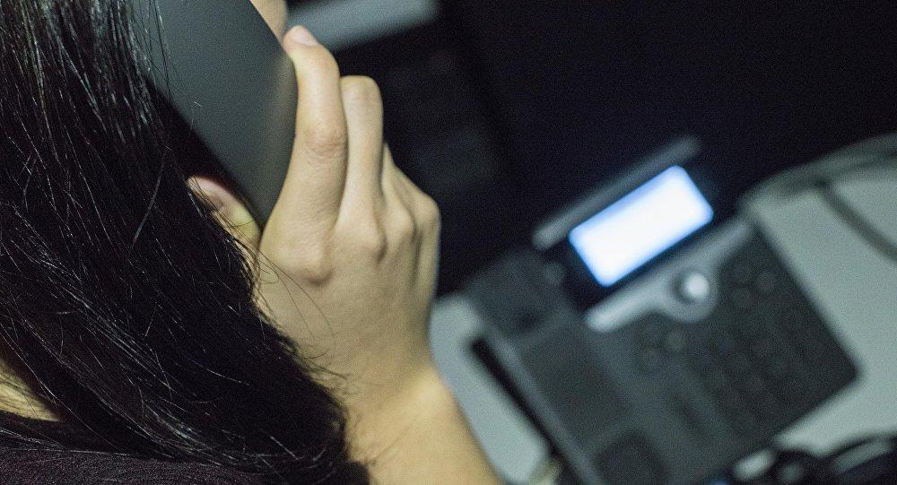 Телефондо сүйлөшүп аткан адам. Архивдик сүрөт