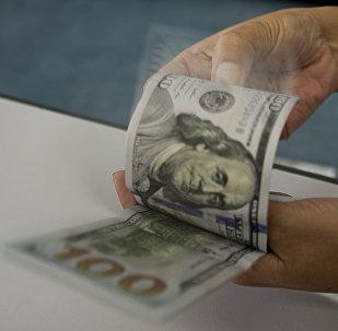 Сотрудник подсчитывает доллары США в обменном бюро. Архивное фото