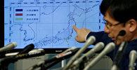 Директор Японского метеорологического агентства Кодзи Накамура указывает на карту с указанием информации о землетрясениях во время пресс-конференции в Токио
