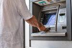 Архивное фото мужчины который снимает деньги в банкомате