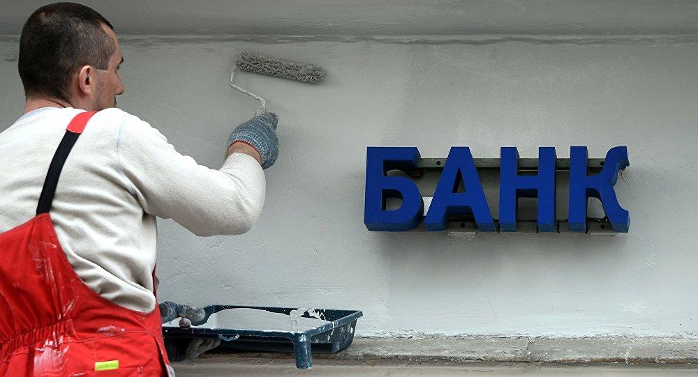 Рабочий красит фасад здания банка. Архивное фото