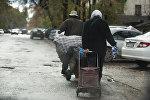 Люди с сумками идут на одном из улиц Бишкека. Архивное фото