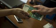 Передача пачки денег. Иллюстративное фото