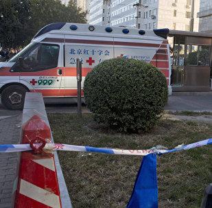 Сотрудник полиции Китая и карета скорой помощи на месте происшествия. Архивное фото