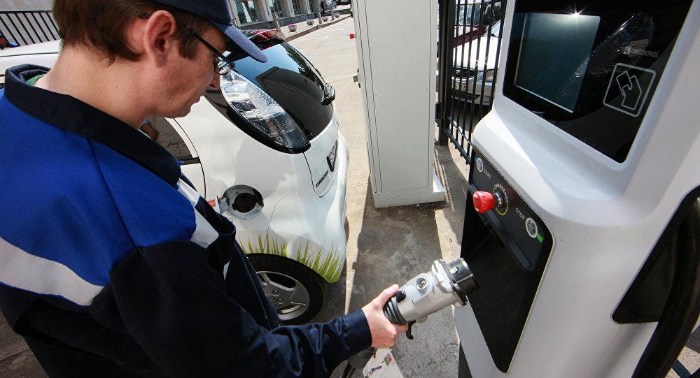 Сотрудник заряжает электромобиль на станции быстрого заряда. Архивное фото