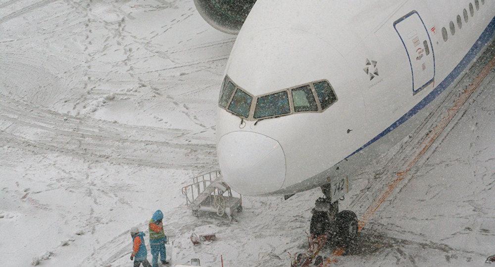 Сотрудники аэропорта у самолета во время снегопада. Архивное фото