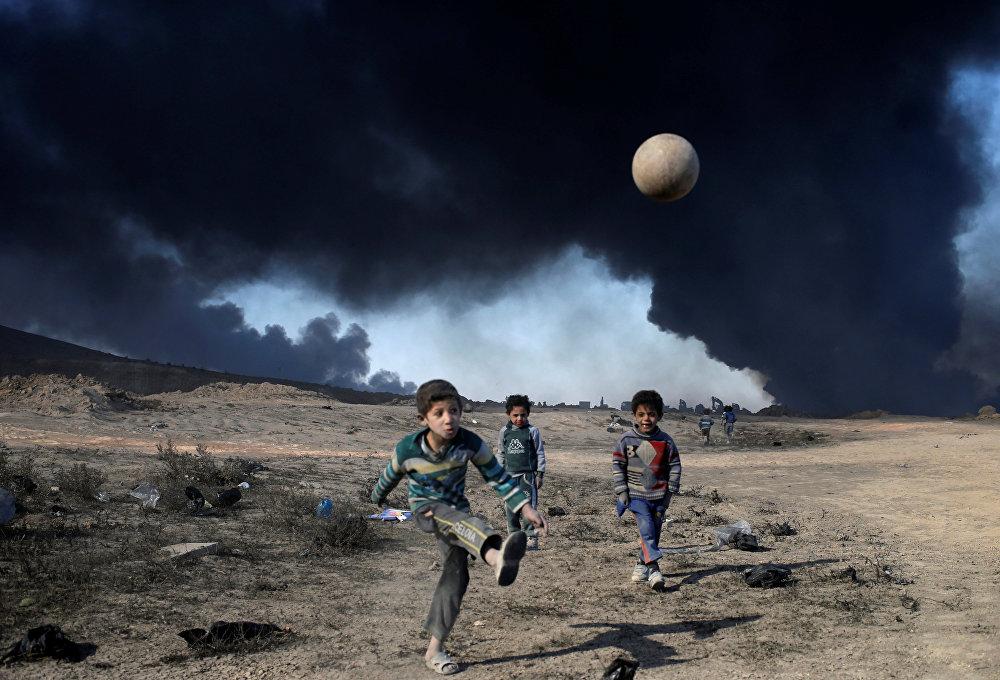 Буга чейин Ислам мамлекети террордук уюму тарабынан өрттөлгөн мунай чыккан жерде футбол ойноп жаткан Ирактагы балдар