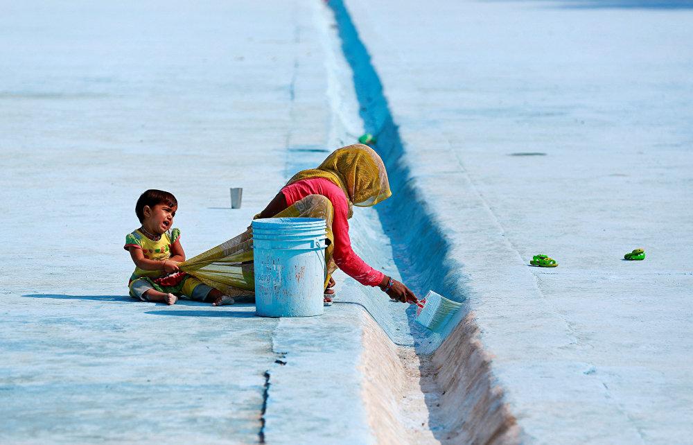 Делидеги көлмөнүн түбүн боеп жаткан аял (Индия)