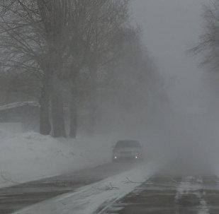 Автомобильное движение на дорогах во время сильного снегопада и метели. Архивное фото