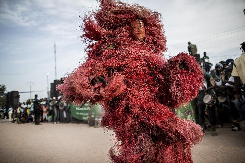 Канкуранг — Африкадагы мандинка элинин диний кийимин кийип алып бийге түшкөн киши. Мындай костюм адатта баланы отургузганда жана күнөөлөрдөн арылып жатканда кийилет. Сүрөттө 1-декабрда өткөн президенттик шайлоо алдындагы иш-чара. Брикама, Гамбия