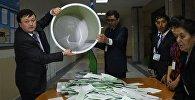 Выемка бюллетеней членами избирательной комиссии на избирательном участке во время выборов президента Узбекистана.