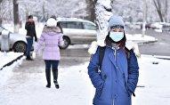Девушка в медициной маске на одной из улиц Бишкека. Архивное фото