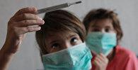 Дети в масках смотрят на градусник. Архивное фото