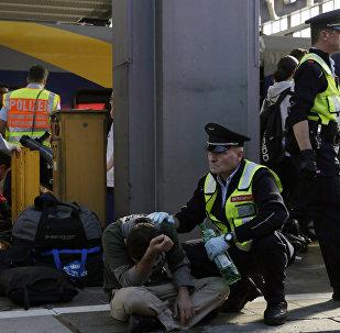 Мюнхендин вокзалында полиция кызматкерлери жана Сириядан келген мигрант. Архивдик сүрөт