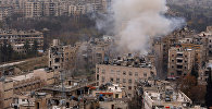 Дым после взрыва в районе, контролируемого сирийской армией в Алеппо. Архивное фото